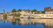stock photo of zurich  - Zurich view across the Limmat river from the Rudolf Brun bridge towards the Lindenhof park in summer early morning - JPG