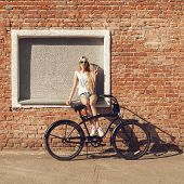 pic of swag  - Young woman with city bicycle near brick wall - JPG