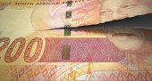 stock photo of nelson mandela  - A concept picture of a regular South African two hundred rand note tearing in two length ways on an isolated background - JPG
