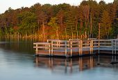 pic of dock a pond  - Morning sunrise shines over pier illuminating autumn colors on trees and calm lake creates a peaceful scene - JPG