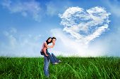 image of shoulder-blade  - Young man giving girlfriend a piggyback ride against cloud heart - JPG