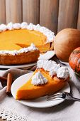 image of pumpkin pie  - Composition of homemade pumpkin pie on plate and fresh pumpkins on wooden background - JPG