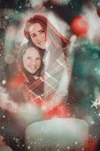 stock photo of blanket snow  - Festive mother and daughter wrapped in blanket against candle burning against festive background - JPG