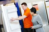 stock photo of mall  - shop assistant demonstrates refrigerator to young woman in home appliance shopping mall supermarket - JPG