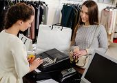 stock photo of cashiers  - Happy woman customer paying with credit card in fashion showroom - JPG