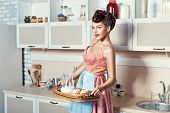 stock photo of apron  - Woman holding a tray with dessert she in the kitchen wearing an apron - JPG