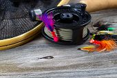 picture of fly rod  - Close up of fly reel focus on front of reel with fly jig hanging from spool - JPG