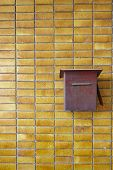 stock photo of postbox  - Yellow Tiles Wall With Red Rusty Postbox Home decoration - JPG