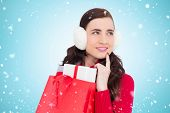 pic of muffs  - Brunette with ear muffs holding shopping bag full of gifts against blue vignette - JPG