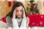 picture of pain-tree  - Brunette getting a headache on christmas day against fir tree forest and snowflakes - JPG