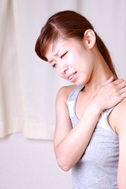 stock photo of stiff  - young Japanese woman suffers from stiff neck - JPG