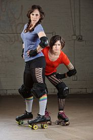picture of roller-derby  - Pair of tough Caucasian female roller derby skaters - JPG
