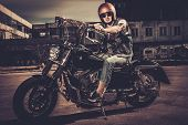 stock photo of ape-man  - Tattooed biker and his bobber style motorcycle on a city streets  - JPG