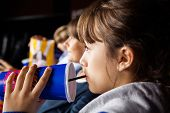 picture of watching movie  - Closeup of girl drinking cola while watching movie with family in cinema theater - JPG