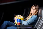 pic of movie theater  - Side view portrait of smiling woman with snacks sitting at movie theater - JPG