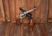 foto of revolver  - Two revolvers with bullets on a wooden background - JPG