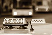 pic of headlight  - auto emblem and sign of a taxi against city streets with the vague image of buses and the included headlights in tone sepia - JPG