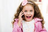 stock photo of unbelievable  - portrait of cute little happy girl using cell phone looking surprised - JPG