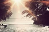 pic of infinity pool  - Bright sunburst over a luxury tropical infinity pool framed with palm trees overlooking the ocean on the island of Maldives in a travel concept - JPG