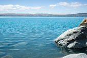 stock photo of off-shore  - Rocky and very scenic western shore of Lake Pukaki just off the road to Aoraki - JPG
