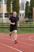 image of race track  - healthy man run on athletics race sport track and representing concept of sport and speed - JPG