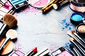 image of cosmetic products  - Colorful frame with various makeup products on dark background - JPG