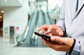 image of escalator  - Business Man Using Mobile while going down Escalator - JPG