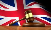 picture of jacking  - Law and justice of United Kingdom concept with a 3d rendering of a gavel on a wooden desktop and the Union Jack Uk flag on background - JPG