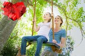 foto of swing  - Happy mother swinging daughter at park against heart - JPG