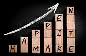 picture of ascending  - Message MAKE IT HAPPEN on ascending arrow above bar graph of Wooden small cubes isolated on black background - JPG