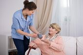 picture of geriatric  - Young caregiver caring about elder lady at home - JPG