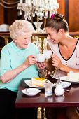 picture of granddaughter  - Senior woman and granddaughter drinking coffee and eating cake in cafe - JPG