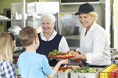 pic of pupils  - Pupils In School Cafeteria Being Served Lunch By Dinner Ladies - JPG