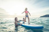 picture of watersports  - family having fun in the water and teaching how to stand on the surf to their daughter - JPG
