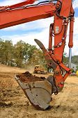pic of track-hoe  - A large track hoe excavator digs dirt and rock for a new fill layer on a commercial construciton road project - JPG