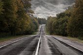 foto of storms  - Dark asphalt road under a storm sky - JPG