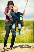 foto of swings  - Mother and her little son having fun together at the playground - JPG