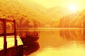 picture of pier a lake  - Wooden boat at pier on mountain lake - JPG