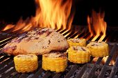 stock photo of flames  - Grilled BBQ Chicken Breast and Corn Rings Close-Up. Hot Flaming Grill In The Background.