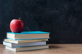 pic of red back  - Apple and a stack of books on desk with blackboard in background - JPG