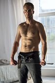 Handsome guy topless with whip BDSM poster