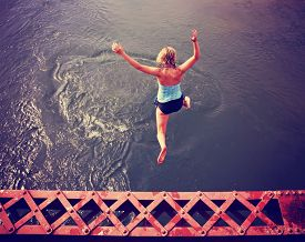 stock photo of trestle bridge  -  a girl jumping of an old train trestle bridge into a river toned during summer time toned with a retro vintage instagram filter effect - JPG