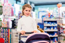 foto of baby doll  - Little girl playing with baby doll carriage in toy store - JPG