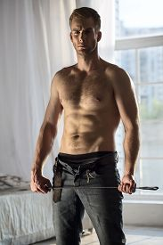 pic of denim jeans  - Handsome guy topless with jeans unbuttoned playfully holding a whip BDSM - JPG