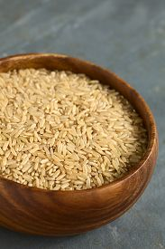 picture of rice  - Raw brown or wholegrain rice kernels in wooden bowl photographed on slate with natural light  - JPG