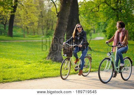 poster of Two young women ride bikes in the spring park. Gentle spring greens yellow dandelions clean air. Pleasure by nature and movements. Healthy lifestyle.