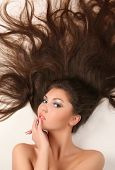 stock photo of brown-haired  - attractive young adult lying on white background with flowing hair - JPG
