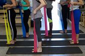 Fit women performing stretching exercise with resistance band in gym poster