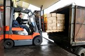 stock photo of heavy equipment operator  - Electric forklift in warehouse loading cardboard boxes - JPG