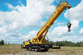 stock photo of risen  - yellow automobile crane with risen telescopic boom outdoors over blue sky - JPG